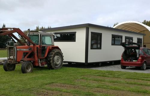 A Cosy Home being moved on its wheels by a Tractor